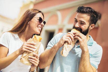 Young couple is eating sandwiches and having a great time