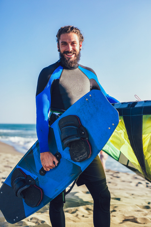 Handsome Caucasian man professional surfer standing  on the sandy beach with his kite and board. Stock Photo