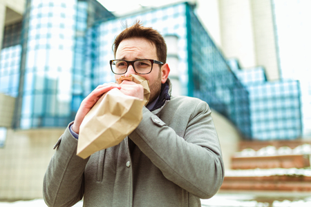 Businessman holding paper bag over mouth as if having a panic attack