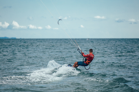 Kitesurfing Kiteboarding action photos man among waves quickly goes Stock Photo - 107904957