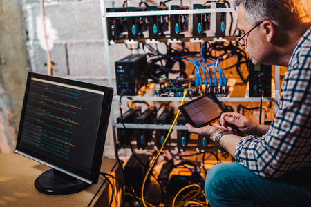 Programmer adjusting cryptocurrency mining rig to optimal operational settings