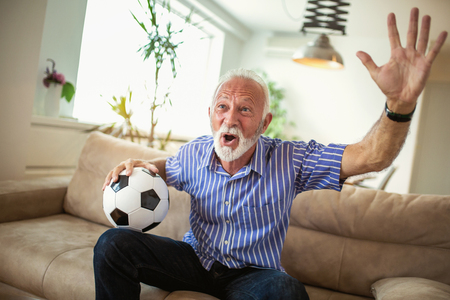 Senior man cheering watching a football game on television Stock Photo
