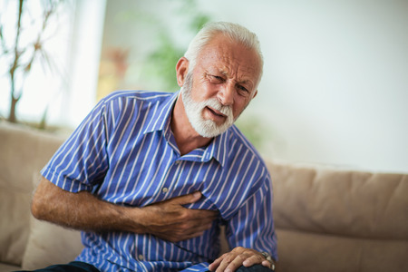Senior man suffering from heart attack at home Banco de Imagens
