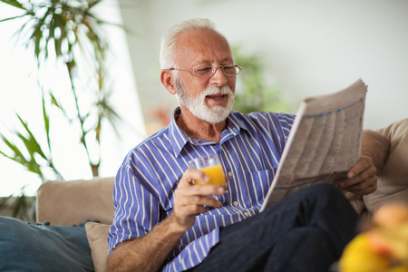 Senior man at home reading newspaper and holding fresh juice