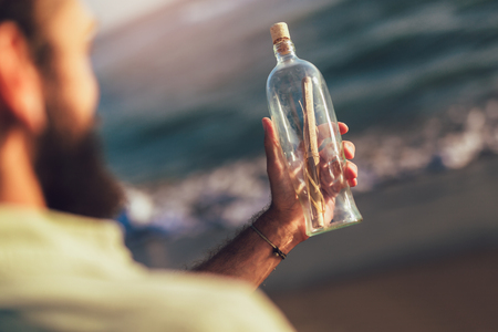 Man by the beach with message in a bottle