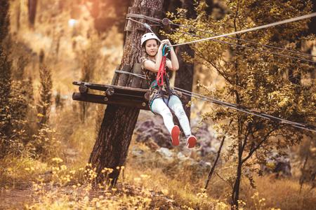 Happy school girl enjoying activity in a climbing adventure park on a summer day Stock fotó - 108466668