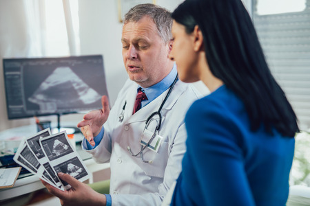 Gynecologist doctor showing ultrasound image to pregnant woman at hospital Stock Photo
