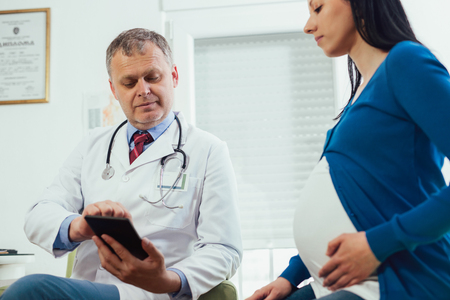 Gynecologist doctor showing ultrasound image on digital tablet to pregnant woman at hospital Stock Photo