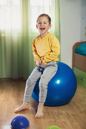 Flat feet correction exercise. Little boy walking over spiked half balance massage balls