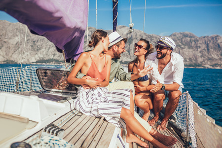 Smiling friends sitting on sailboat deck and having fun.Vacation, travel, sea, friendship and people concept Archivio Fotografico