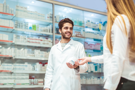 Experienced pharmacist counseling female customer in modern pharmacy Stock Photo