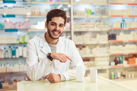 Friendly male pharmacist dispensing medicine holding a box of tablets Banque d'images