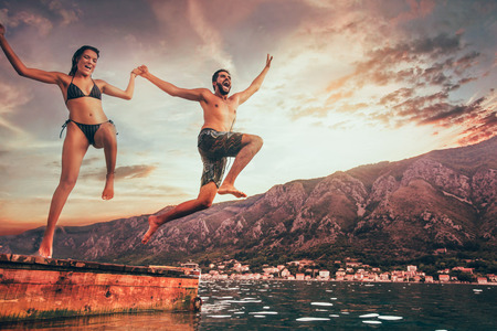 Young couple jumping from a pier into the water