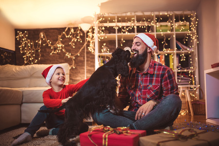 Christmas happy boy and father with puppy.
