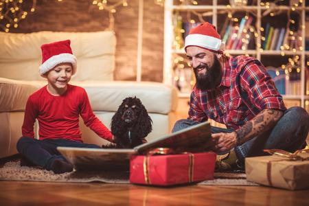 Father and son reading book for Christmas eve Stock Photo
