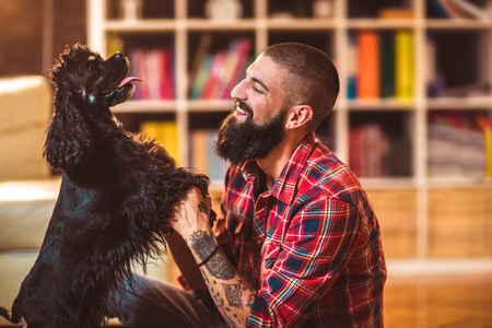 Handsome man with cute dog at home