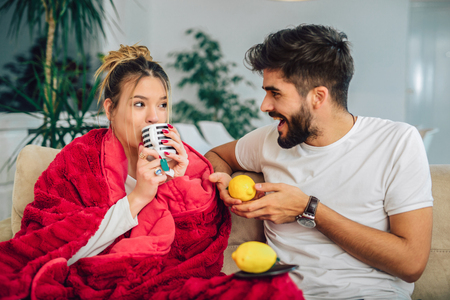 Handsome man taking care of his sick girlfriend lying on the sofa Stock Photo