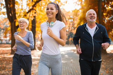 상급 남자와 여자와 젊은 여성 강사는 신선한 공기에서 운동합니다. 야외 활동, 건강한 생활 방식, 강인한 몸, 맞는 인물. 스타일리시하고 모던한 스포츠웨어. 다른 세대