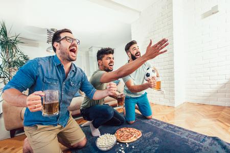 Gelukkige mannelijke vrienden die naar sport kijken op tv en bier drinken.