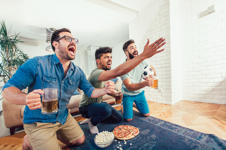 Happy male friends watching sports on tv and drinking beer. Фото со стока