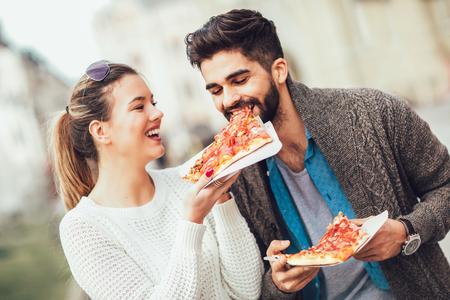 Paare, die draußen Pizza essen und lächeln.