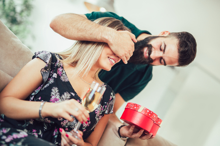 Smiling young man surprising cheerful woman with a gift box at home