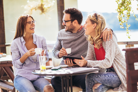 Cheerful group of friends having fun in cafe, using digital tablet. Stock fotó