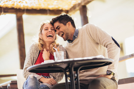 Beautiful loving couple sitting in a cafe enjoying in coffee and conversation. Love, romance, dating
