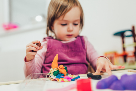 Kid girl is playing with plasticine while sitting at table in nursery room. Stockfoto