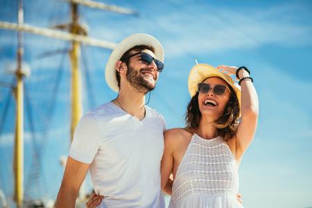 Feliz pareja joven caminando por el puerto de un balneario turístico con veleros en el fondo Foto de archivo