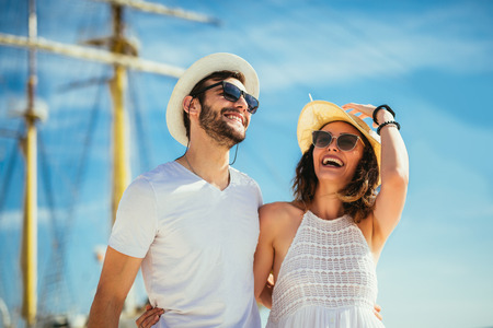 Happy young couple walking by the harbor of a touristic sea resort with sailboats on background Stock Photo - 110789460
