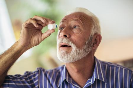 Ältere Person mit Augentropfen Standard-Bild