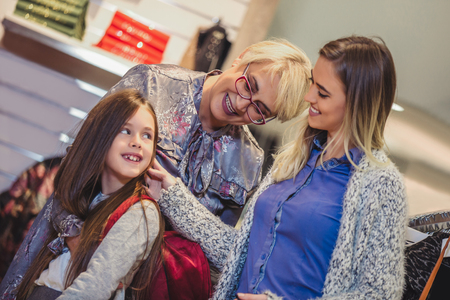 Mother, adult daughter and granddaughter in shopping mall together Stock Photo