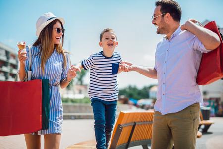 Glückliche Familie, die Spaß im Freien nach dem Einkaufen hat Standard-Bild