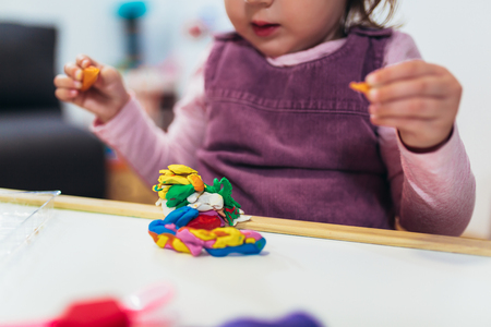 Kid girl is playing with plasticine while sitting at table in nursery room. Stock fotó