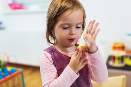 Kid girl is playing with plasticine while sitting at table in nursery room. Banco de Imagens