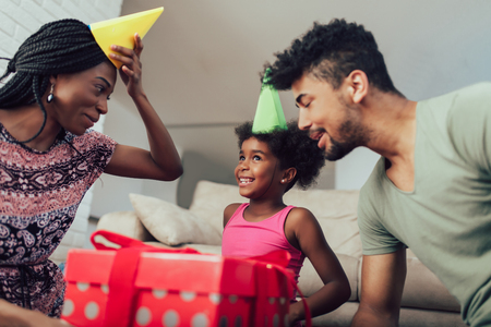 Happy black family at home. African american father, mother and child celebrating birthday, having fun at party. Young woman giving gift to daughter Stock Photo