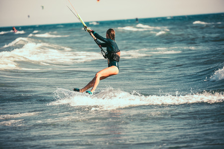 Kite surfing girl in swimsuit with kite in blue sea riding waves with water splash.