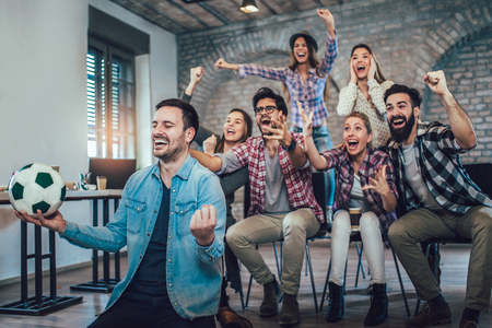 Happy friends or football fans watching soccer on tv and celebrating victory. Friendship, sports and entertainment concept. Stok Fotoğraf