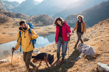 Group of hikers walking on a mountain at autumn day near the lake. Stock Photo