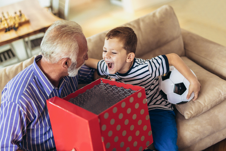 Handsome senior grandfather presenting gift to happy grandson Stock Photo