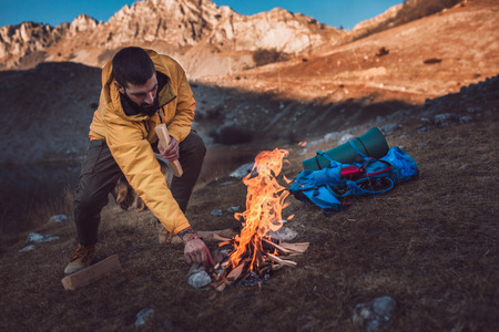 Young hiking man kindling firewood in the mountain