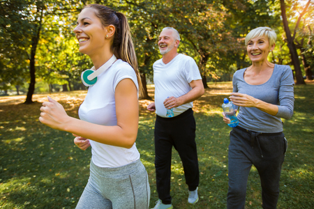 Senior man and woman and young female instructor  workout on fresh air. Outdoor activities, healthy lifestyle, strong bodies, fit figures.