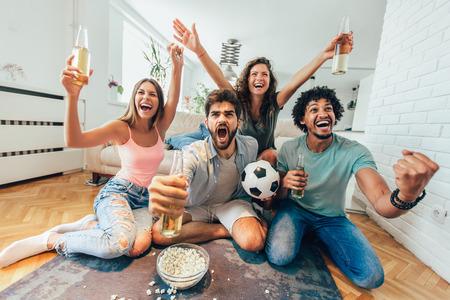 Gelukkige vrienden of voetbalfans die voetbal op TV kijken en thuis overwinning vieren. Vriendschap, sport en vermaakconcept. Stockfoto