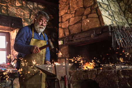 Blacksmith manually forging the molten metal on the anvil in smithy with spark fireworks Фото со стока - 113230890