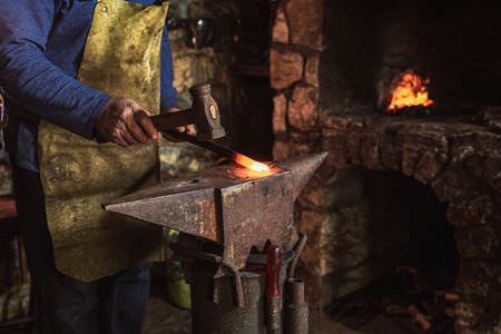 Blacksmith manually forging the molten metal on the anvil in smithy with spark fireworks