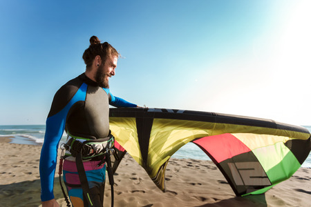 Handsome Caucasian man professional surfer standing on the sandy beach with his kite Stock fotó
