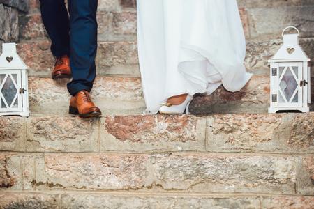 Novia y el novio de la boda de pie uno al lado del otro en el matrimonio. Piernas de novios.