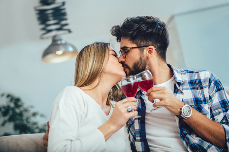 Young couple enjoying wine at home.They are sitting close to each other and drinking red wine.