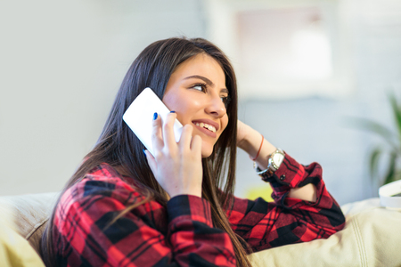 Shot of a charming young woman enjoying a conversation on her mobile phone while sitting on sofa at home.  Stock Photo